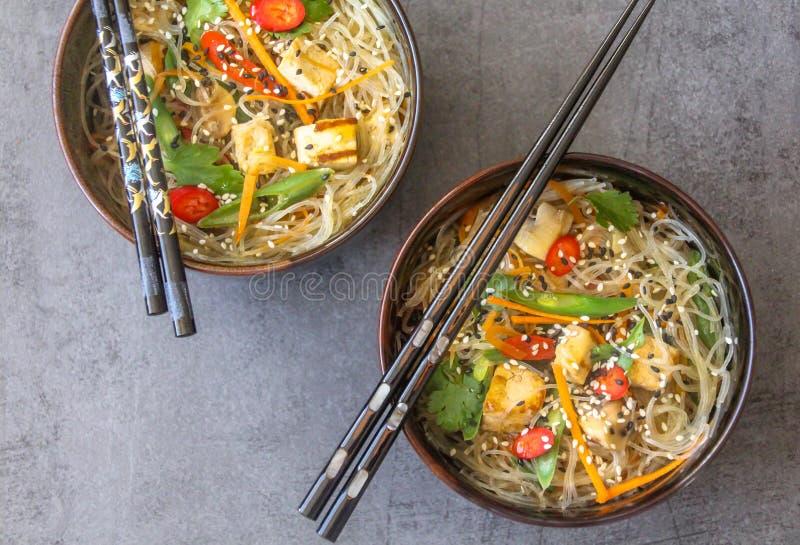 Bästa sikt av två orientaliska plattor med en strikt vegetarianmaträtt av exponeringsglasnudlar, tofuen och nya grönsaker arkivbild
