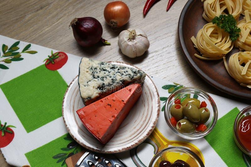 Bästa sikt av två typer av ost och oliv på bakgrunden av pasta, löken, vitlök och peppar på en servett fotografering för bildbyråer