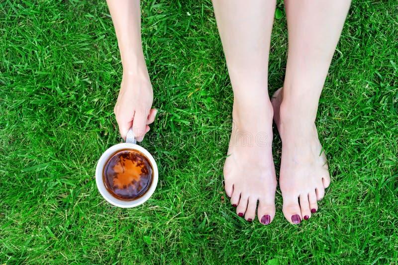 Bästa sikt av unga ben för vuxen kvinna och hållande kopp tesammanträde för hand på gräsmatta för grönt gräs Sjukvård Avslappnand royaltyfri bild