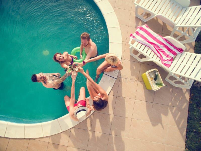 Bästa sikt av unga flickor och pojkar i simbassängen som rostar med royaltyfria foton