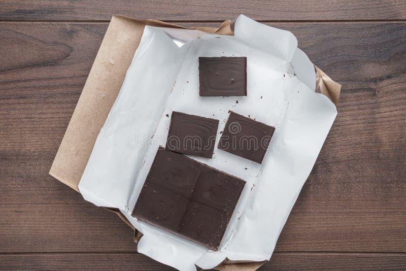 Bästa sikt av uppackade mörka chokladstycken på trätabellen royaltyfri foto