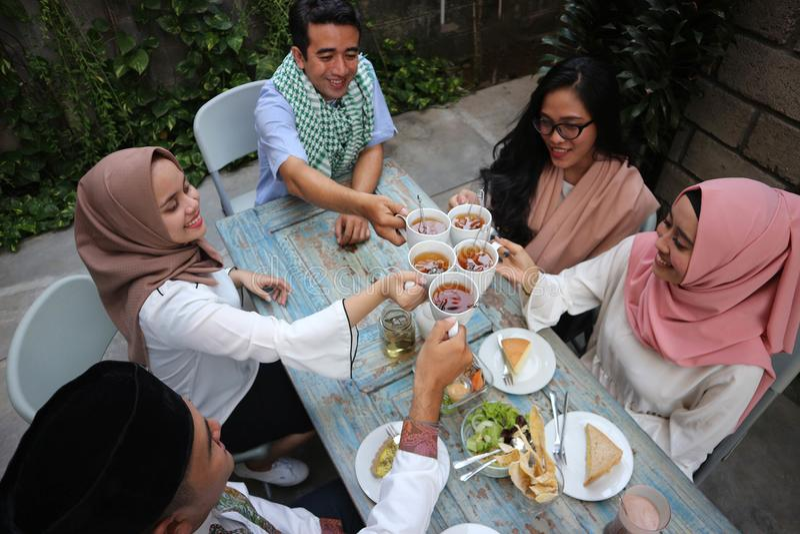 Bästa sikt av vänner för en grupp som har terostat bröd på tabellen som äter middag dur royaltyfri fotografi
