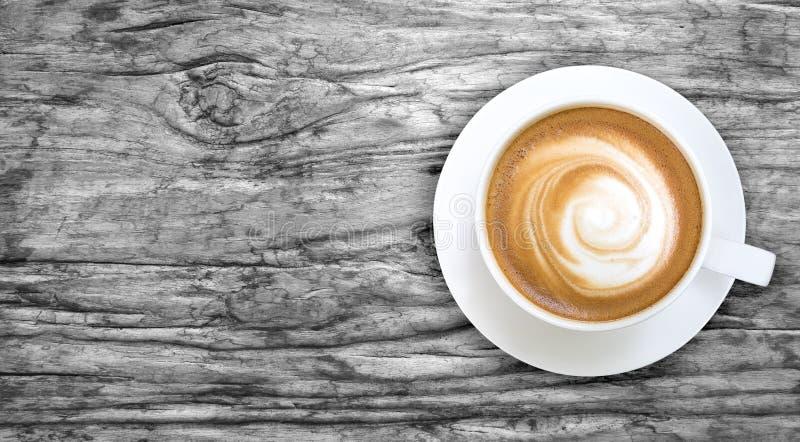 Bästa sikt av varm kaffecappuccino i en vit keramisk kopp på grå färger arkivbilder