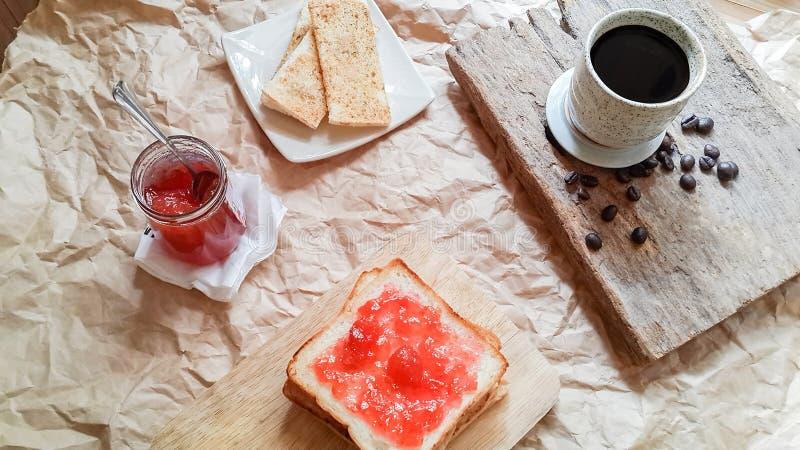 Bästa sikt, bröd med hemlagat jordgubbedriftstopp med varmt kaffe på trä royaltyfria foton