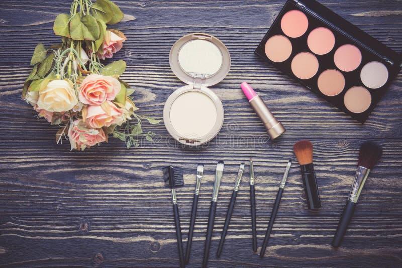 Bästa sikt en samling av kosmetisk makeup och blomman på trätabellbakgrund royaltyfri bild