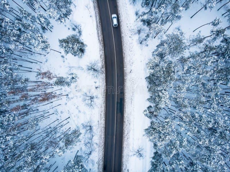 Bästa sikt för flyg- surr av asfaltvägen med bilen bland vinterskog i snö, naturlopp och trans.begrepp arkivbilder