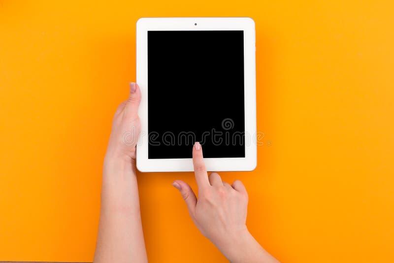 Bästa sikt för närbild av kvinnan som rymmer den digitala minnestavlan med kopieringsutrymme på orange bakgrund arkivbilder