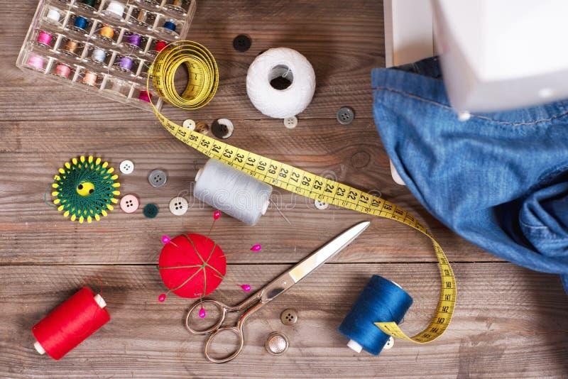 Bästa sikt för sömmerska- eller skräddarebakgrund med jeans som syr hjälpmedel, färgrika trådar, symaskinen och tillbehör arkivbilder