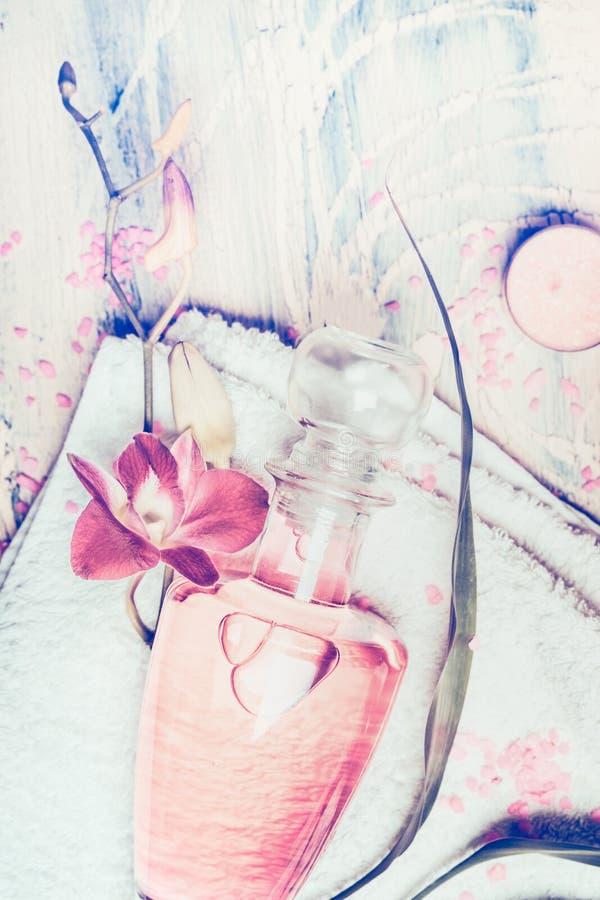 Bästa sikt för Wellness som komponerar med lotionflaskan och orkidén på handduken på sjaskig chic bakgrund fotografering för bildbyråer