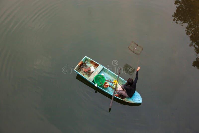 Bästa sikt, fiskare med traditionell krabbafälla som sitter på fartyget i floden av den härliga reflexionen för mangroveskog Trat arkivbild