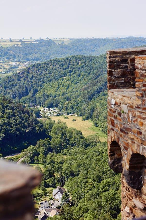 Bästa sikt från slottväggar av den lilla byn som omges av gröna kullar som täckas med skogen arkivbild