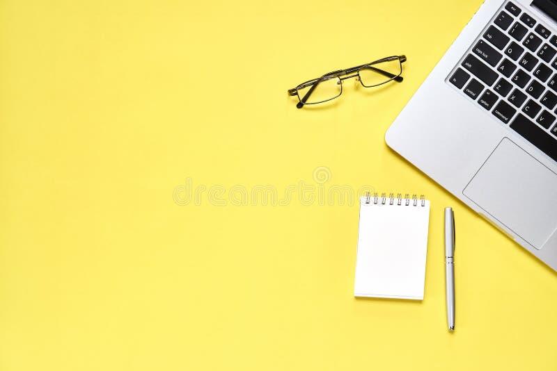 Bästa sikt, modern arbetsplats med bärbara datorn och anteckningsbok med pennan som förläggas på en pastellfärgad gul bakgrund royaltyfri foto