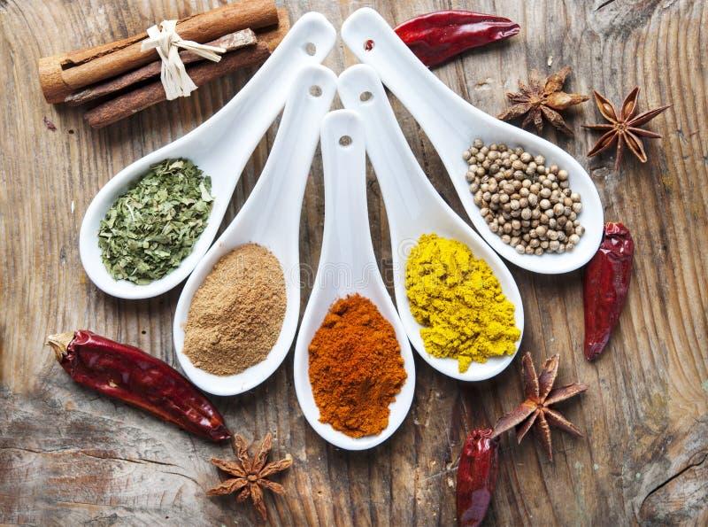 Bästa sikt på blandade torra färgrika kryddor på den trälantliga tabellen royaltyfri fotografi