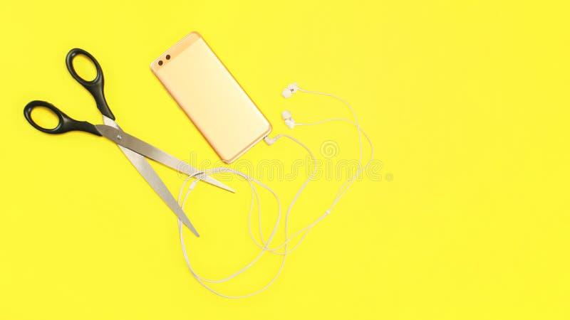 Bästa sikt på den rosa guld- mobiltelefonen med earbudskabel som ska klipps med stor sax på gul bakgrund royaltyfria foton