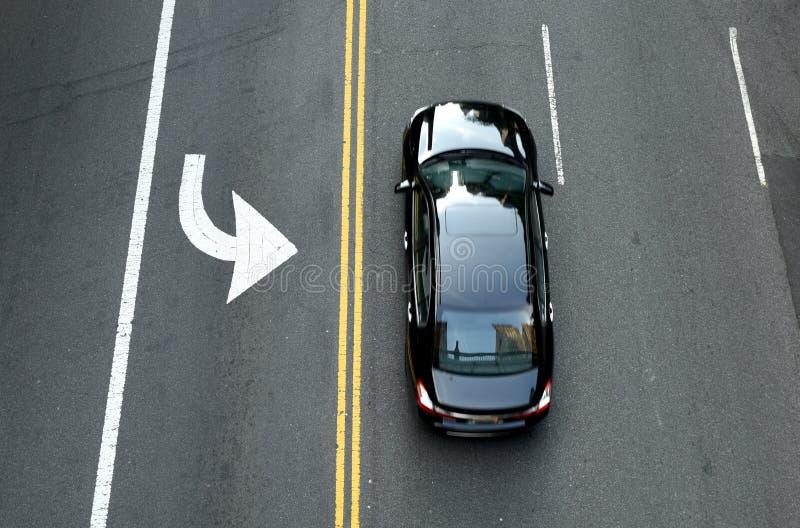 Bästa sikt på den svarta bilen på vägen Dubbel spärrlinje för guling royaltyfria bilder