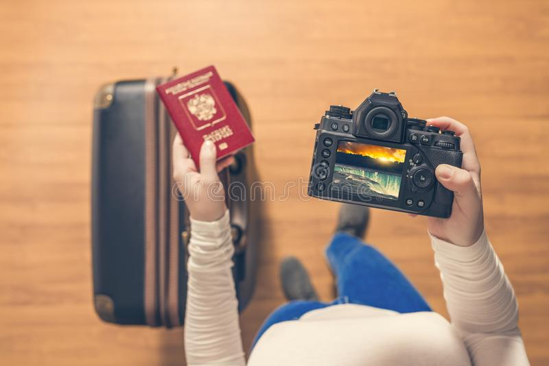 Bästa sikt på en flicka se foto Niagara Falls på hennes kameraanseende med resväskan i flygplatsen Flickan går tillbaka hem efter arkivbilder