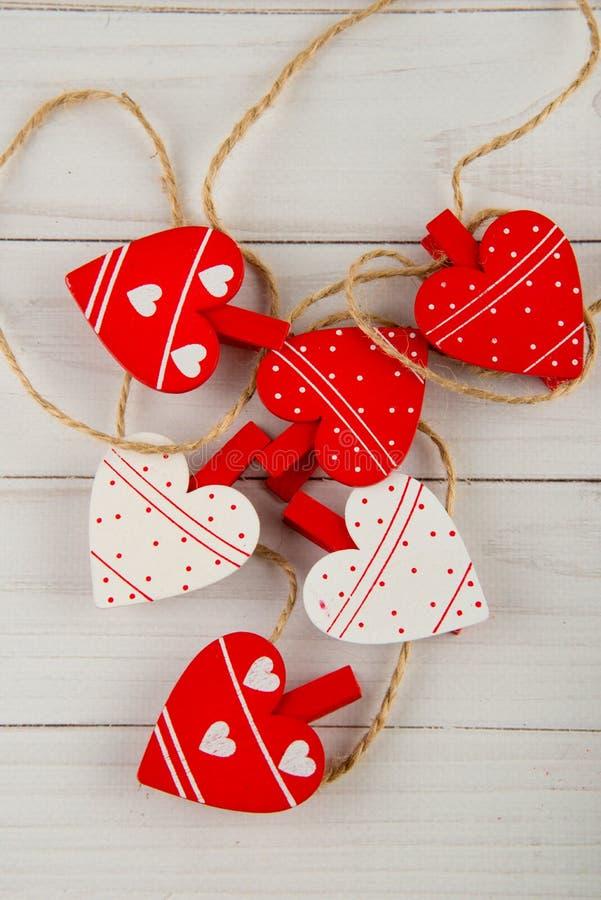 Bästa sikt på gulliga dekorerade vita röda hjärtor som klädnypor på repet som lägger på den vita tabellen arkivbild