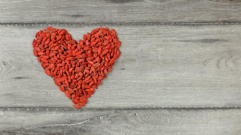 Bästa sikt på hjärtaformsymbolet som göras av wolfberry bär för goji royaltyfria foton