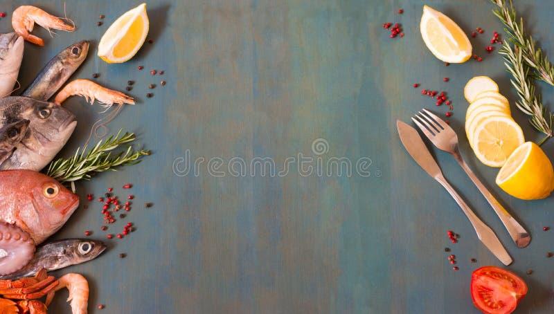 Bästa sikt på ny skaldjur och fisk med fiskkniven och gaffel på en blå träbakgrund med kopieringsutrymme royaltyfri fotografi