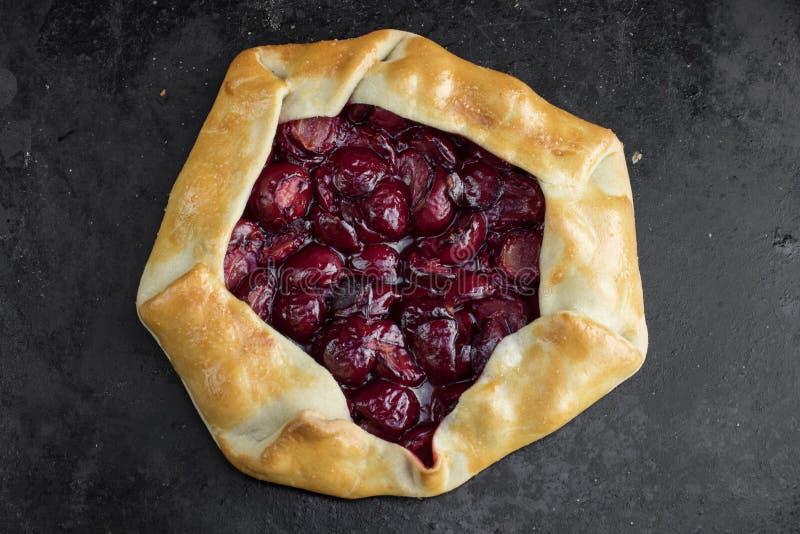 Bästa sikt på Rustical sura Cherry Pie på svart bakgrund arkivfoton