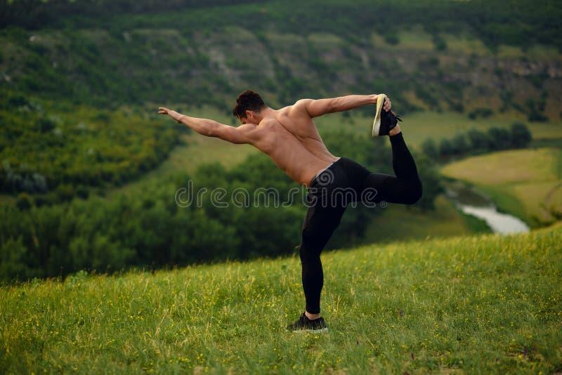Bästa sikt på stenen, ung man för idrottsman nen med den nakna torson i sportswearen som gör sträcka övningar, landskapbakgrund arkivbilder
