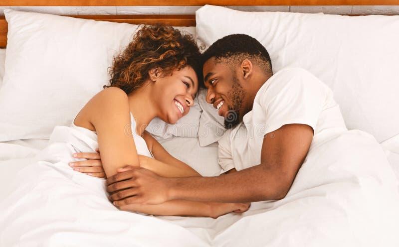 Bästa sikt på unga älska svarta par som ligger i säng arkivfoton