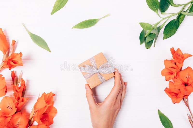 Bästa sikt på vit tabellkvinnligs hand som rymmer den lilla gåvaasken royaltyfri foto