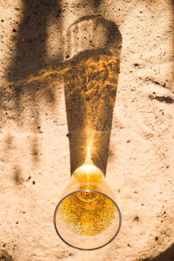 bästa sikt per exponeringsglas av kallt öl på stranden, skuggan av exponeringsglaset på sanden arkivbild