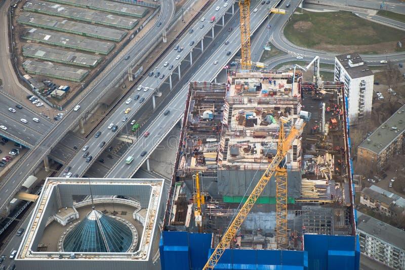 Bästa sikt till konstruktionsplatsen av att resa upp skyskrapan, futured kontor-torn Del av det stora industriella projektet arkivfoto