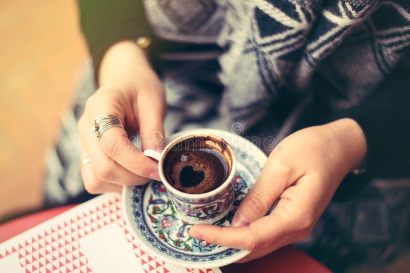 Bästa sikt till turkiskt kaffe i traditionskaffekopp med prydnader i kvinnas händer royaltyfri foto