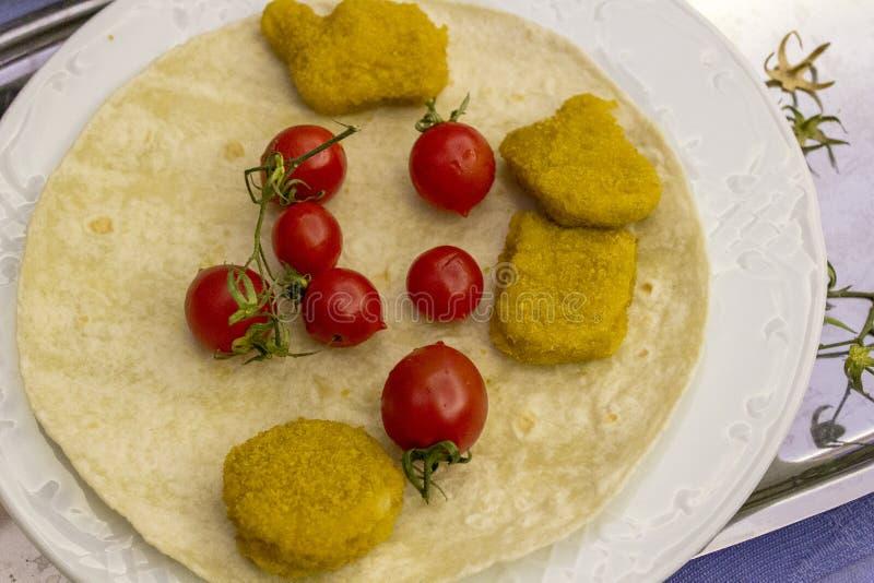 Bästa skott av fega klumpar och små röda nya tomater på den breda vita plattan som en frukost arkivbild