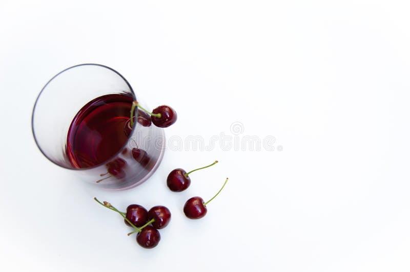 Bästa skott, slut upp av den nya söta körsbäret med vattendroppar, körsbärsröd fruktsaft i exponeringsglas på vit bakgrund, selek royaltyfria foton