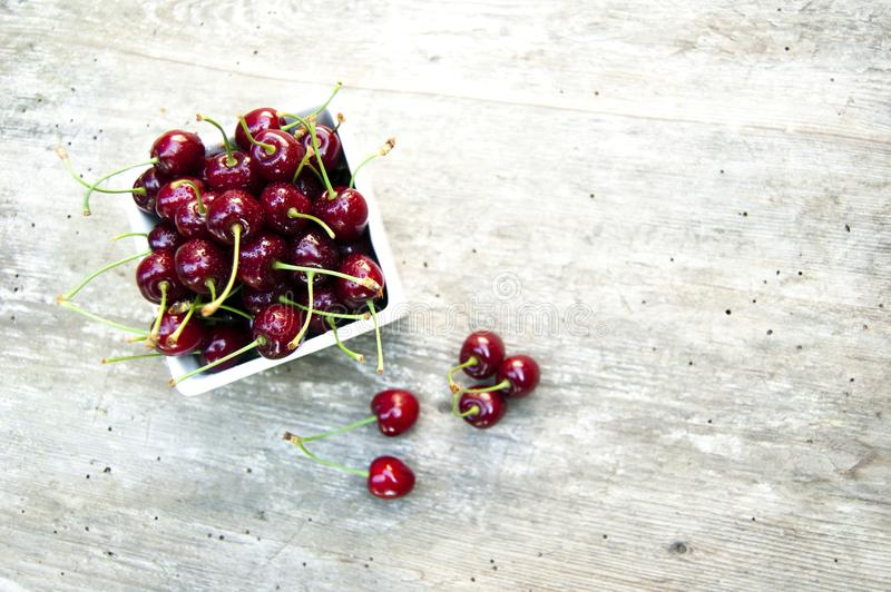Bästa skott, slut upp av den nya söta röda körsbäret i den vita bunken på lantlig träbakgrund, selektiv fokus, utrymme för text, arkivfoton