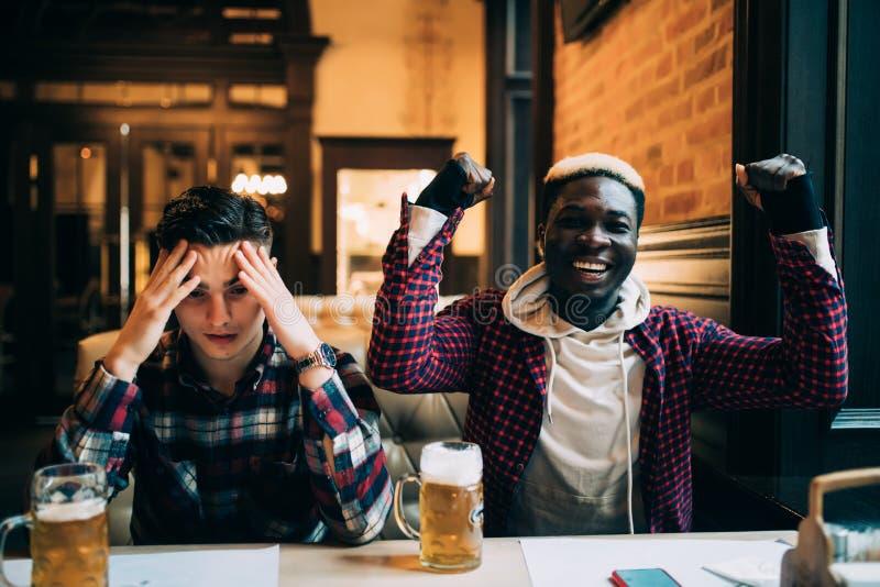 Bästa vän i en stång Lyckligt rop för afro- amerikansk man hans lagställning medan annan manrubbning Manvänner som dricker öl och royaltyfria foton