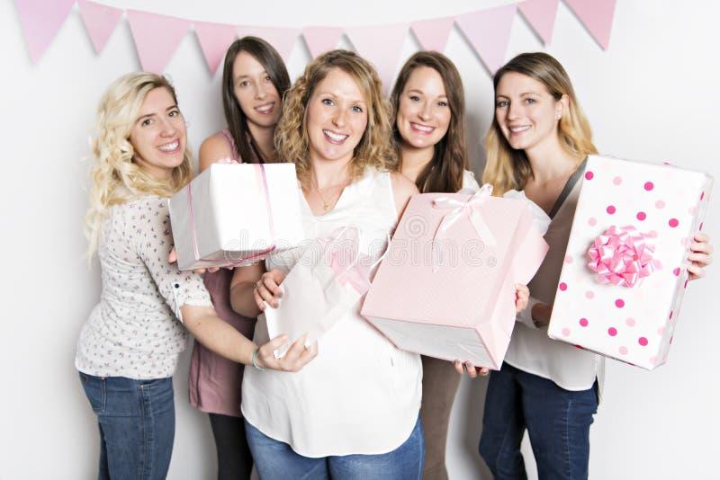 Bästa vän på baby showerpartiet som firar ge ungematerial som gåva arkivbild
