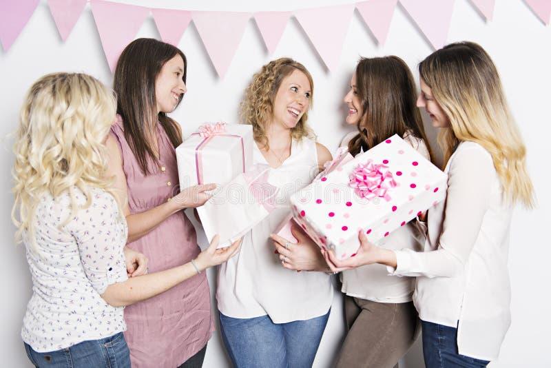 Bästa vän på baby showerpartiet som firar ge ungematerial som gåva arkivfoton
