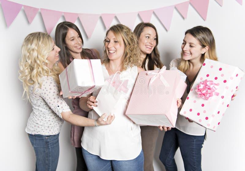 Bästa vän på baby showerpartiet som firar ge ungematerial som gåva arkivbilder