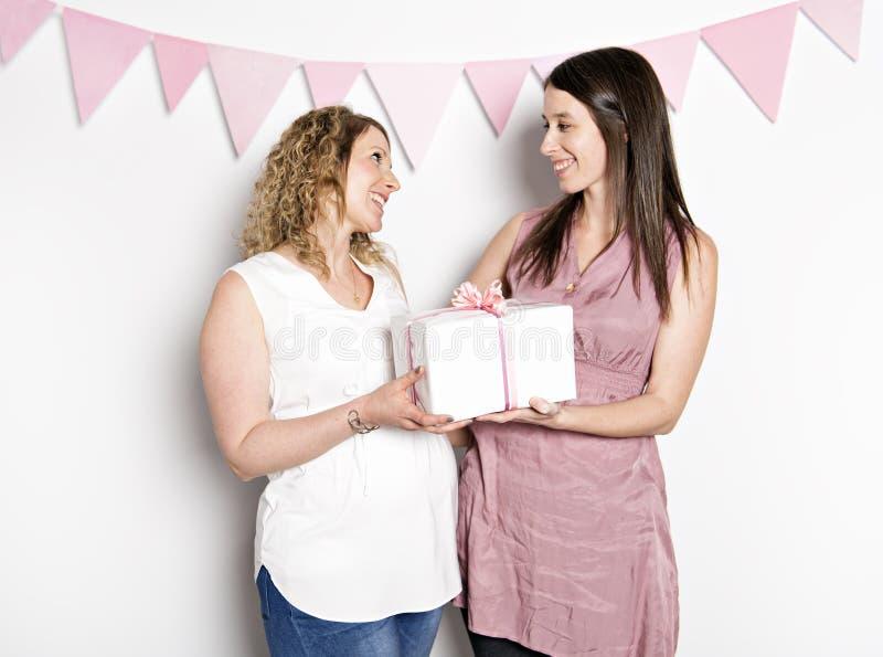 Bästa vän på baby showerpartiet som firar ge ungematerial som gåva royaltyfri fotografi