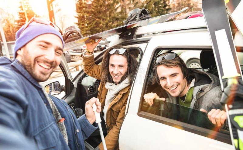 Bästa vän som har gyckel som tar selfie på bilen med, skidar och snowboarden royaltyfria foton