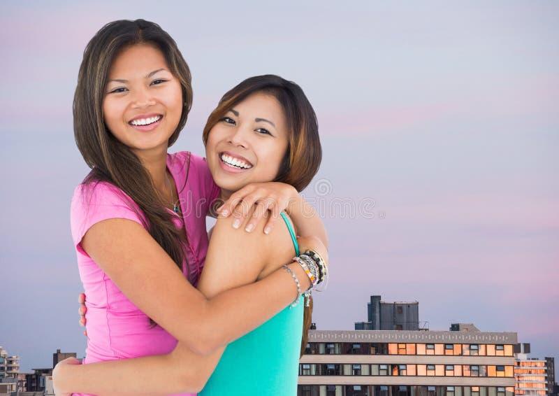 Bästa vän som kramar mot byggnader och aftonhimmel royaltyfri bild