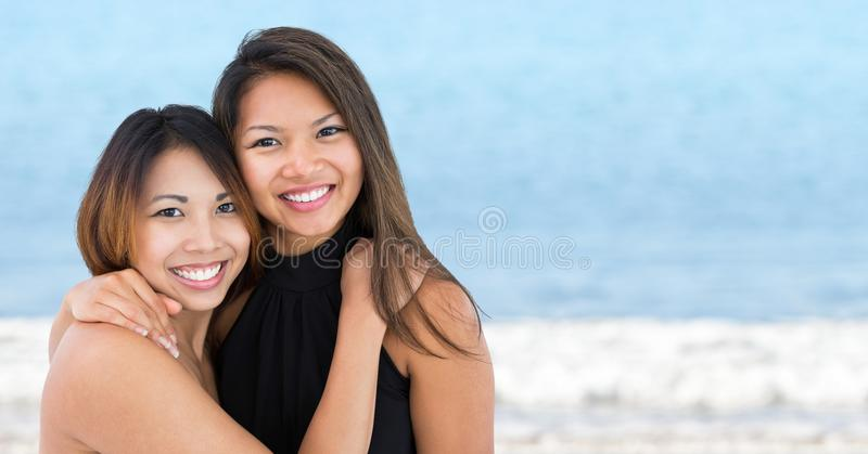 Bästa vän som kramar mot oskarpt vatten arkivfoton