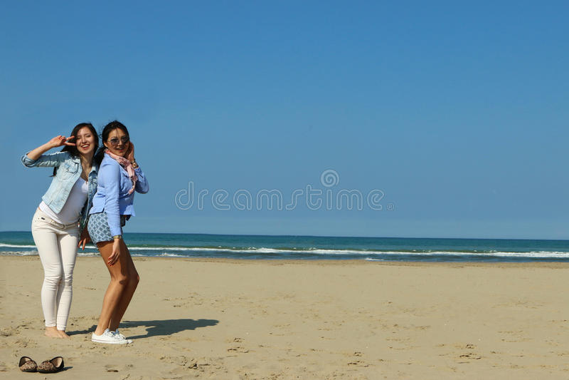 Bästa vän som poserar lyckligt på stranden arkivfoto