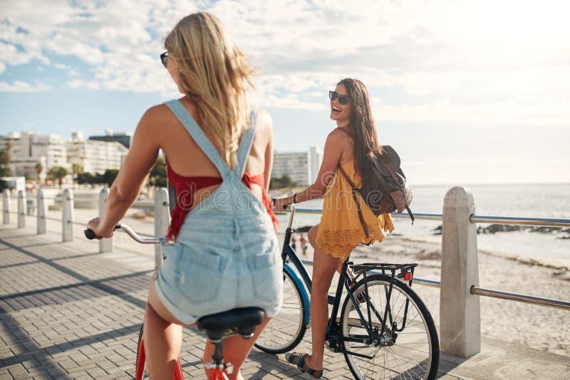 Bästa vän som rider på deras cyklar vid havet arkivfoto