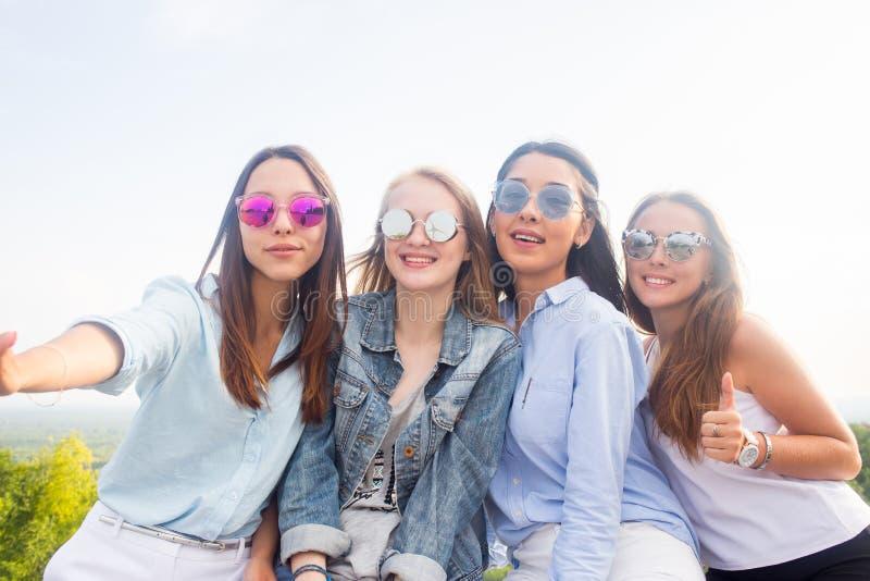 Bästa vän tar selfies, medan gå i parkera Fyra härliga kvinnor som bär solglasögon, har en bra dag royaltyfri foto
