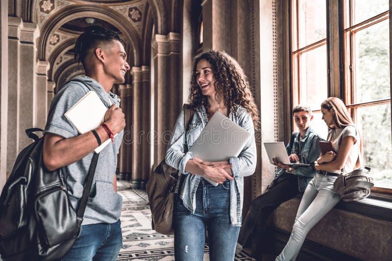 Bästa vän Unga le studenter som står i universitetkorridoren och, talar med de arkivbilder