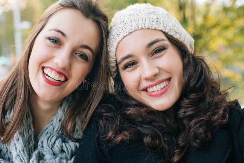 Bästa vänflickor som ler till kameran arkivfoto