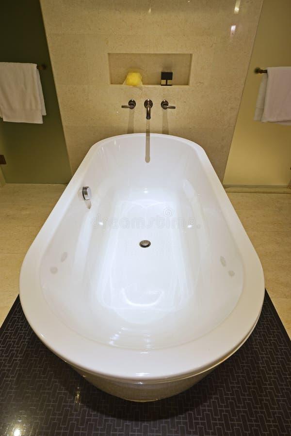 Bästa vertikal sikt av det klassiska designbadrummet med det stora badkaret och den glänsande marmorväggen royaltyfri fotografi