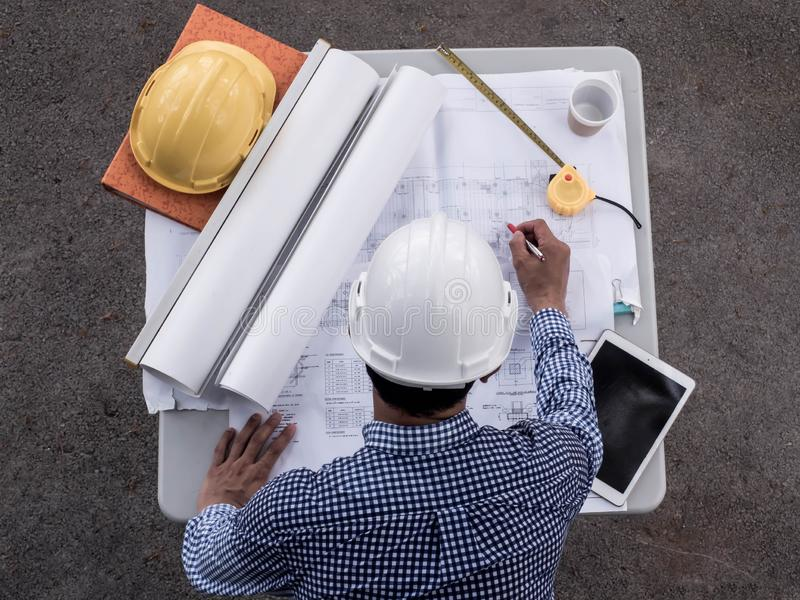 Bästa viwe, teknikerer i hjälmar som planerar nytt projekt på tabellen Arkitekt Working On Blueprint royaltyfri bild