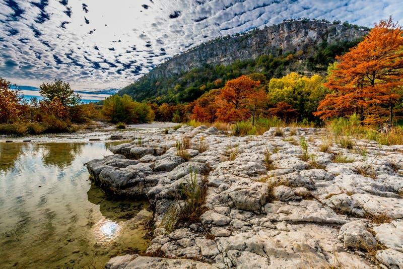 Bäume mit Herbstlaub auf Rocky Bank des Frio-Flusses mit Hügel im Hintergrund lizenzfreie stockbilder