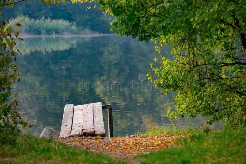 Bäume, See und ein Bootsdock, vervollkommnen für Meditation, an einem schönen Herbsttag Natürliche Rahmenfalllandschaft mit Baums stockbild